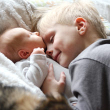 A 5 year old big brother is hugging, smiling, and looking at his newborn baby sister as they sunggle in bed.